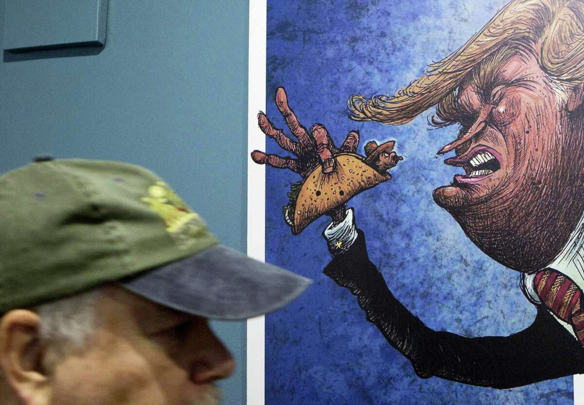 """An American visitor walks past a cartoon of a Mexican wrapped in a taco sticking his tongue out at a depiction of President-elect Donald Trump, in an exhibition titled; """"Trump: A wall of caricatures,"""" at the Caricature Museum in downtown Mexico City, Thursday, Nov. 10, 2016. The exhibition, which features dozens of works by Mexican and international cartoonists, mocks amongst other things Trump's derogatory statements about Mexicans and his plans to build a wall between the two countries.(AP Photo/Rebecca Blackwell)"""