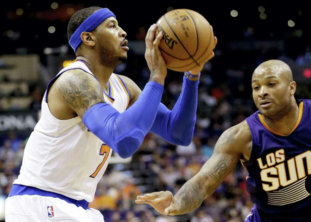 New York Knicks' Carmelo Anthony shoots as Phoenix Suns' P.J. Tucker defends during the first half of an NBA basketball game, Wednesday, March 9, 2016, in Phoenix. (AP Photo/Matt York)