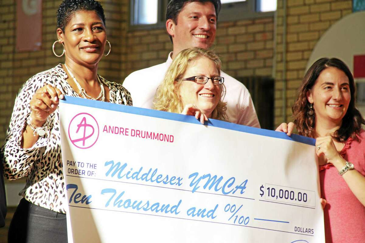 Christine Cameron, left, mother of Andre Drummond, presents a $10,000 donation to Michele Rulnick, the president of the Y, along with Robert Mosca, Director of Major Gifts, Wesleyan University, and Kori Termine Wisneski, a Middlesex YMCA board member, in 2013. That donation has funded Andre's All-stars program.
