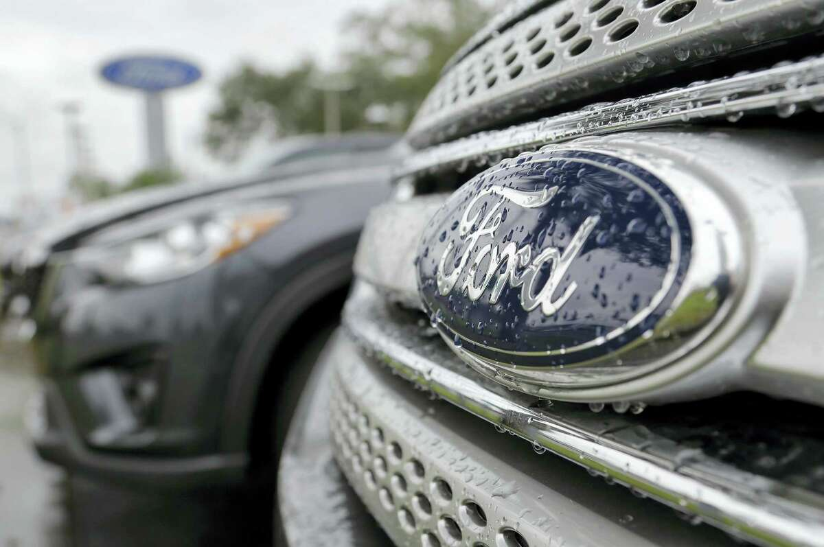 In this Jan. 12, 2015 photo, Ford vehicles sit on the lot at a car dealership, in Brandon, Fla. Ford Motor Co. expects its pretax profit to fall in 2017 but improve in 2018 as it invests in emerging businesses. Ford updated its outlook Wednesday, Sept. 14, 2016 at its annual investor day.