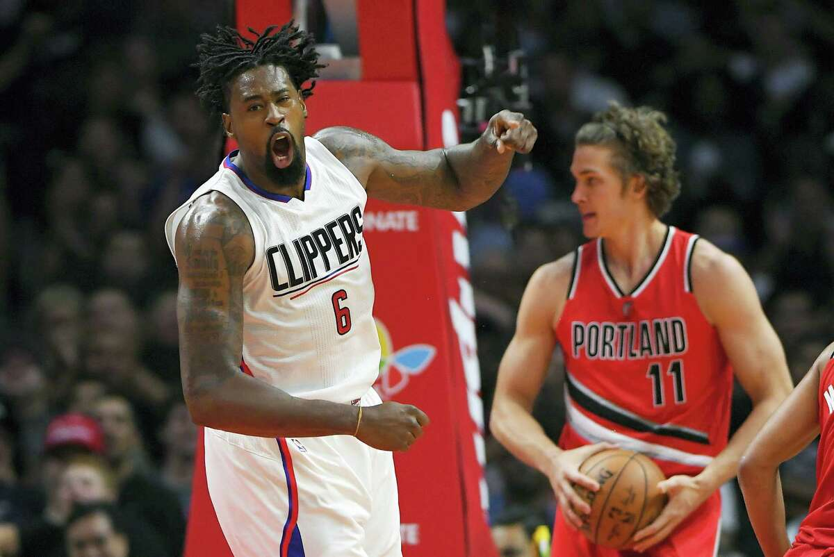 Los Angeles Clippers center DeAndre Jordan, left, celebrates after scoring as Portland Trail Blazers forward Meyers Leonard takes the ball during the second half of an NBA basketball game on Wednesday, Nov. 9, 2016 in Los Angeles. The Clippers won 111-80.