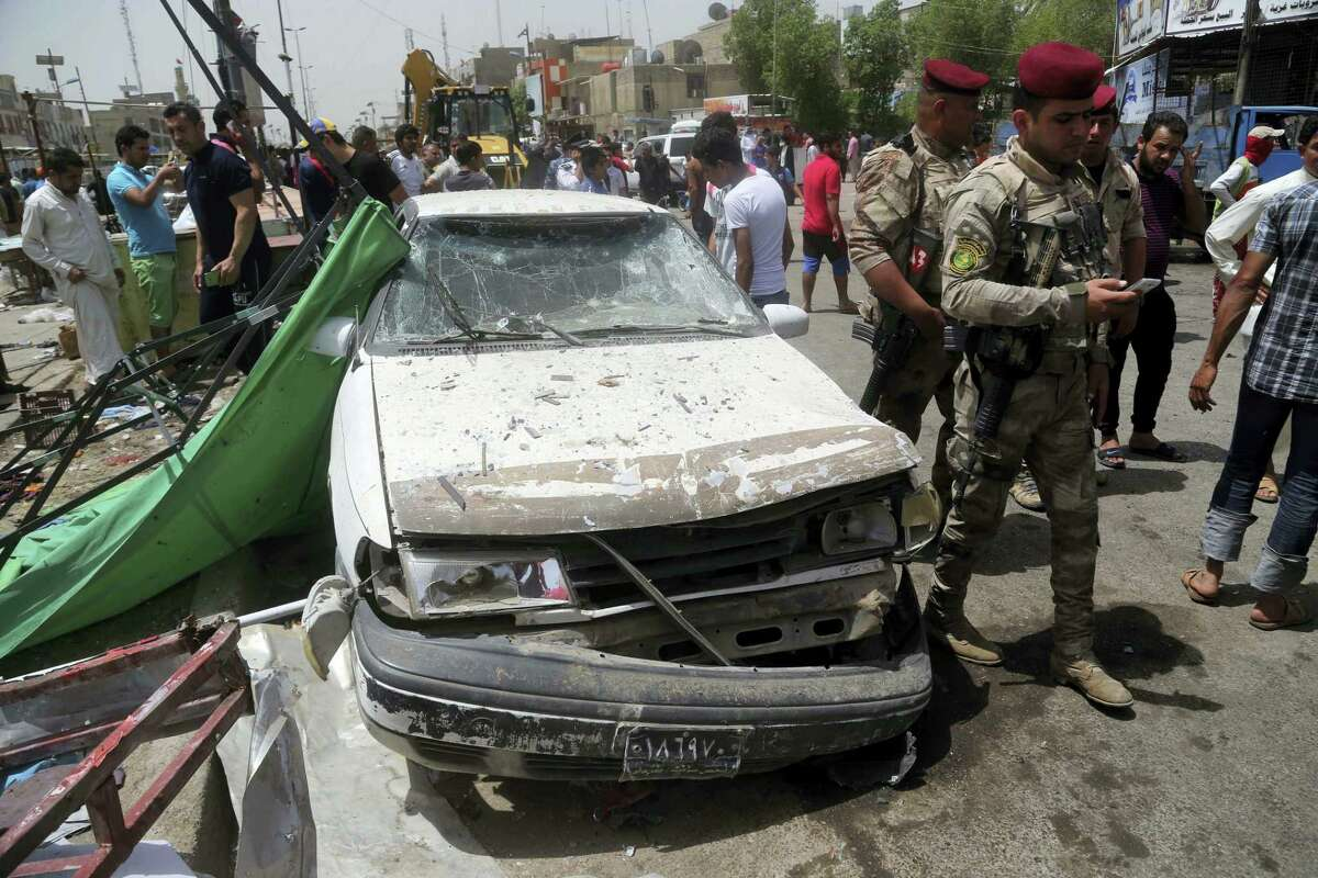 Security forces and citizens inspect the scene after a car bomb explosion at a crowded outdoor market in the Iraqi capital's eastern district of Sadr City, Iraq, Wednesday, May 11, 2016. An explosives-laden car bomb ripped through a commercial area in a predominantly Shiite neighborhood of Baghdad on Wednesday, killing and wounding dozens of civilians, a police official said.