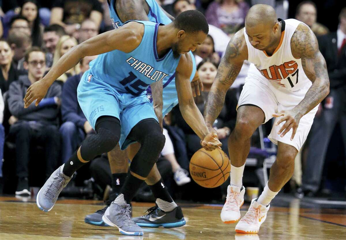 Phoenix Suns' P.J. Tucker (17) and Charlotte Hornets' Kemba Walker (15) battle for a loose ball during the first half of an NBA basketball game Wednesday, Jan. 6, 2016, in Phoenix. (AP Photo/Ross D. Franklin)