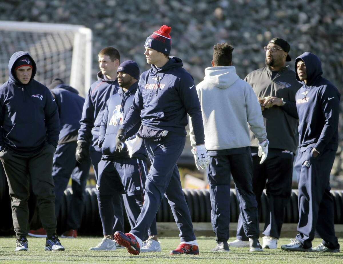 New England Patriots quarterback Tom Brady, center, walks onto the field at the start of an NFL football practice, Wednesday, Jan. 6, 2016, in Foxborough, Mass. The Patriots are to host an NFL divisional playoff game Jan. 16, 2016 in Foxborough, Mass. (AP Photo/Steven Senne)