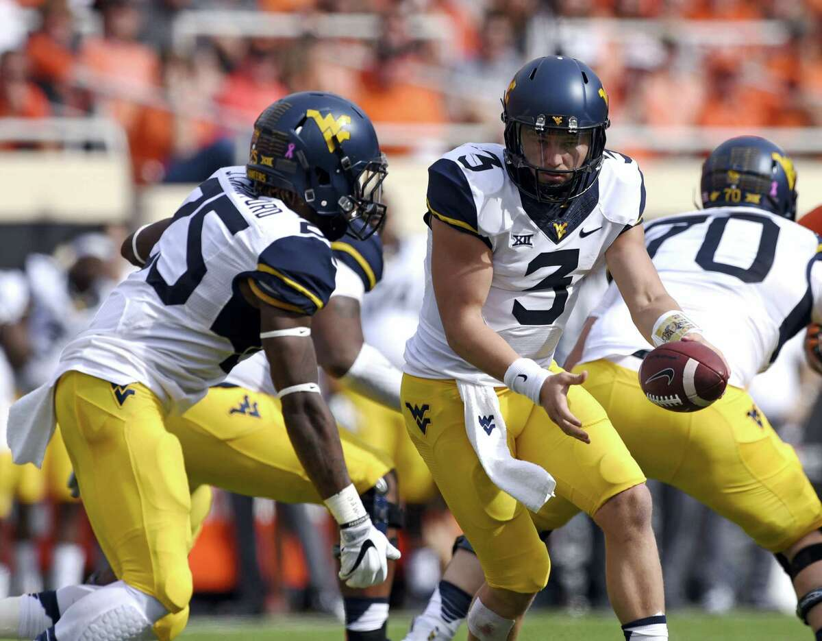 In this Oct. 29, 2016 photo, West Virginia quarterback Skyler Howard (3) hands off to running back Justin Crawford during the team's NCAA college football game against Oklahoma State in Stillwater, Okla. West Virginia travels to play Texas this week.