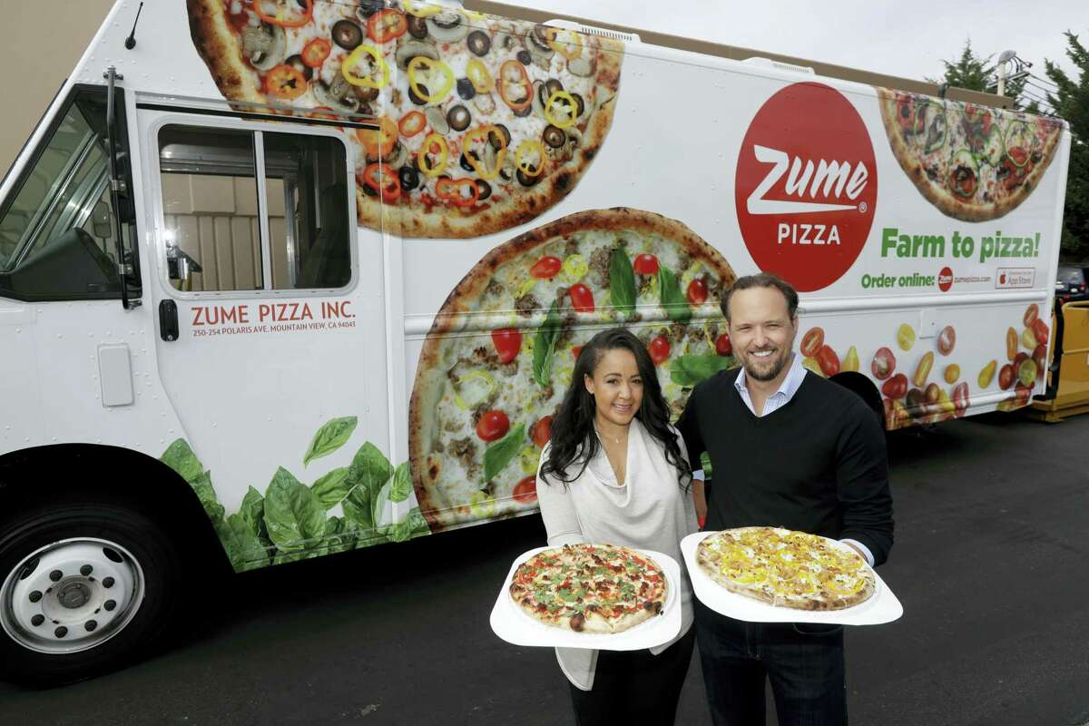 In this Monday, Aug. 29, 2016 photo, CEO and co-founder Julia Collins, left, and co-founder Alex Garden pose for a photo in front of one of the company's delivery trucks at Zume Pizza in Mountain View, Calif. The startup, which began delivery in April, is using intelligent machines to grab a slice of the multi-billion-dollar pizza delivery market. Zume is one of a growing number of food-tech firms seeking to disrupt the restaurant industry with software and robots that let them cut costs, speed production and improve worker safety.