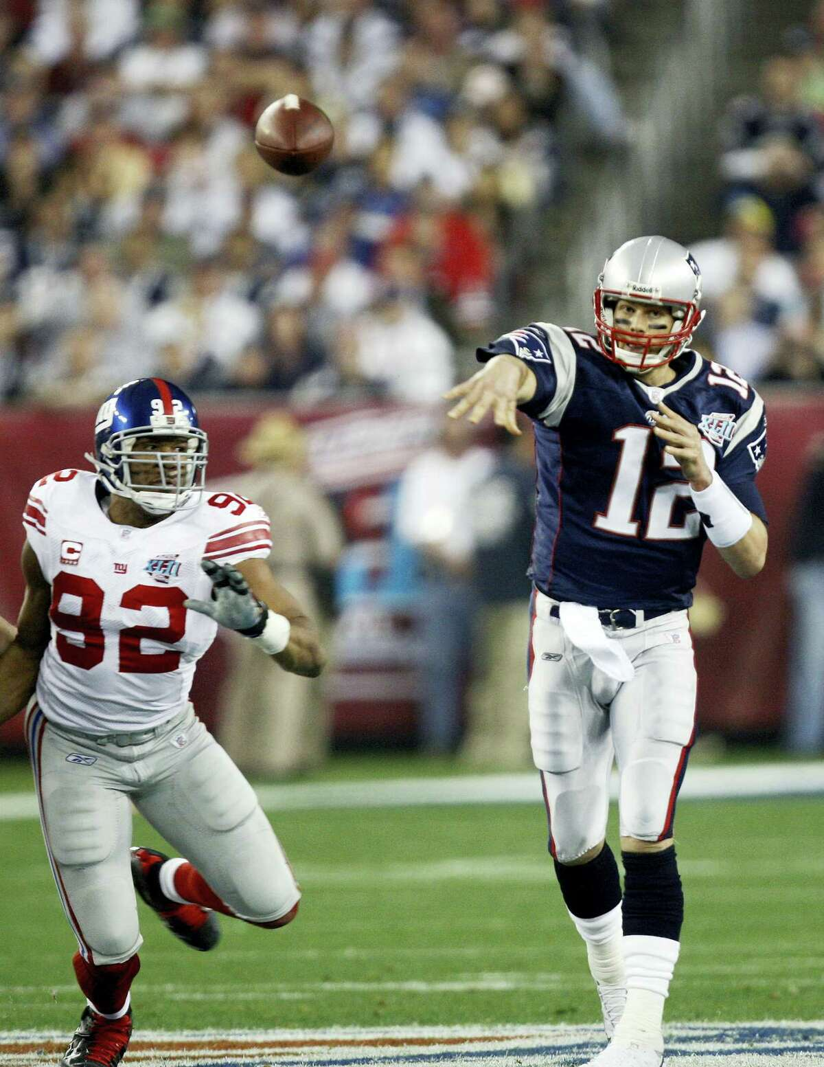 In this Feb. 3, 2008 photo, New England Patriots quarterback Tom Brady, right, throws a pass in front of New York Giants defensive end Michael Strahan during the Super Bowl XLII football game at University of Phoenix Stadium in Glendale, Ariz. The one-time rivals are teaming up to produce a documentary series called the 'Religion of Sports,' to air beginning Nov. 15, 2016, on DirectTV's Audience Network. Each hour-long episode will look at how unique sports competitions are influencing societies and cultures across the globe.
