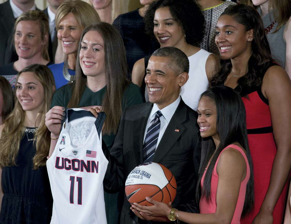 President Barack Obama poses for photographs after being presented with a UConn basketball jersey by Breanna Stewart, second from left, and a commemorative ball by Moriah Jefferson, lower right, in the East Room of the White House Tuesday, Huskies forward Morgan Tuck is upper right.