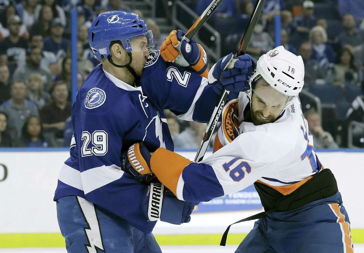 Tampa Bay Lightning defenseman Slater Koekkoek (29) and New York Islanders left wing Andrew Ladd (16) scrap during the first period on Thursday. Ladd was penalized for high-sticking.