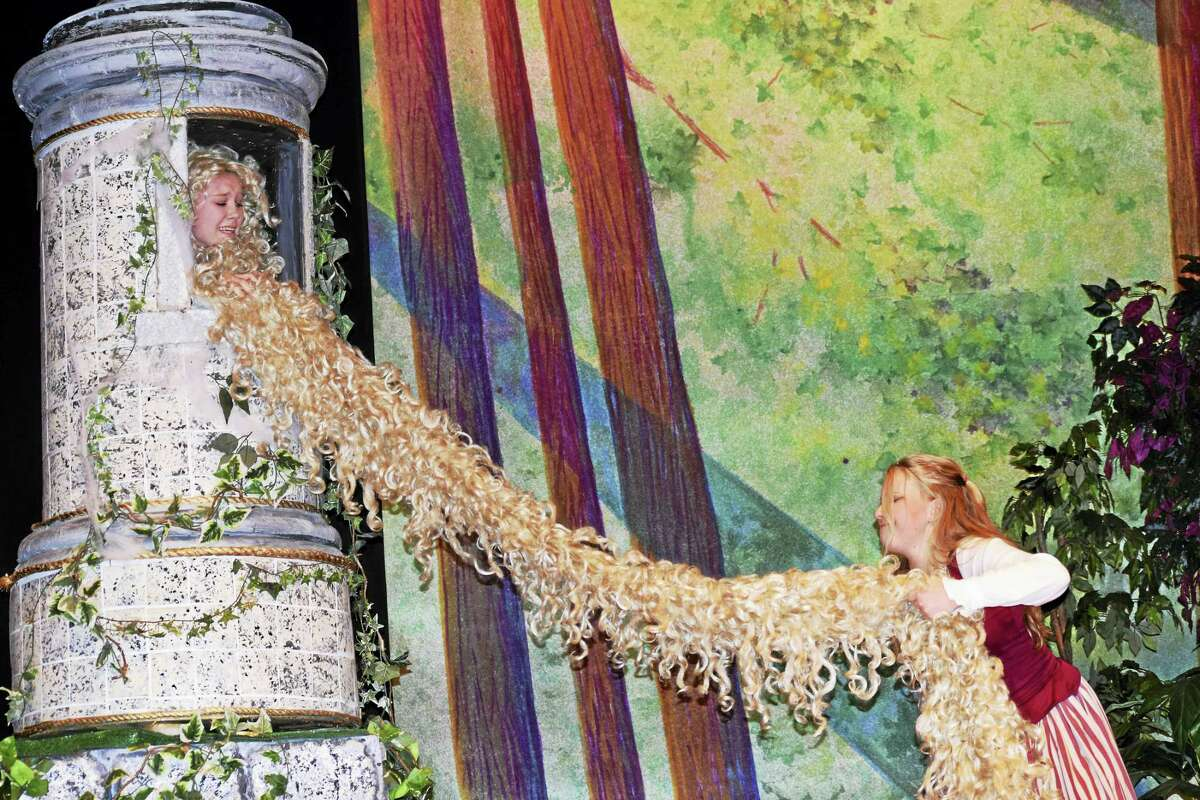 """Baker's Wife tries to get a piece of Rapunzel's hair in this dress rehearsal for Mercy High School's staging of """"Into the Woods. Rapunzel is played by Katrina McGlynn and the Baker's Wife by Betty Smith."""