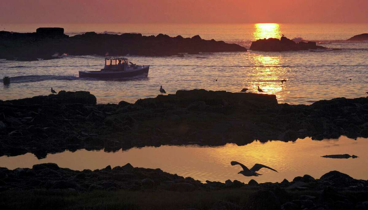 In this Aug. 17, 2015, file photo, a lobsterman motors through a channel between islands as he leaves Cape Porpoise Harbor at sunrise in Kennebunkport, Maine. As most Americans brace themselves for losing an hour of sleep, some corners of the country are proposing bold alternatives to daylight saving time. Lawmakers in a dozen states, from Alaska to Florida, want to abolish the practice of changing clocks twice a year.