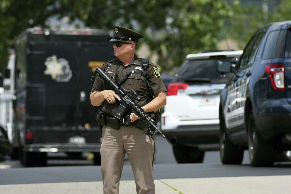 Sheriff's Deputy Guy Puffer stands watch outside the Berrien County Courthouse after a shooting incident in St. Joseph, Mich., Monday, July 11, 2016. A jail inmate trying to escape from the western Michigan courthouse wrested a gun from an officer Monday, killing a few bailiffs and injuring a few more people before he was fatally shot by other officers, a sheriff said. (Mark Parren via AP)