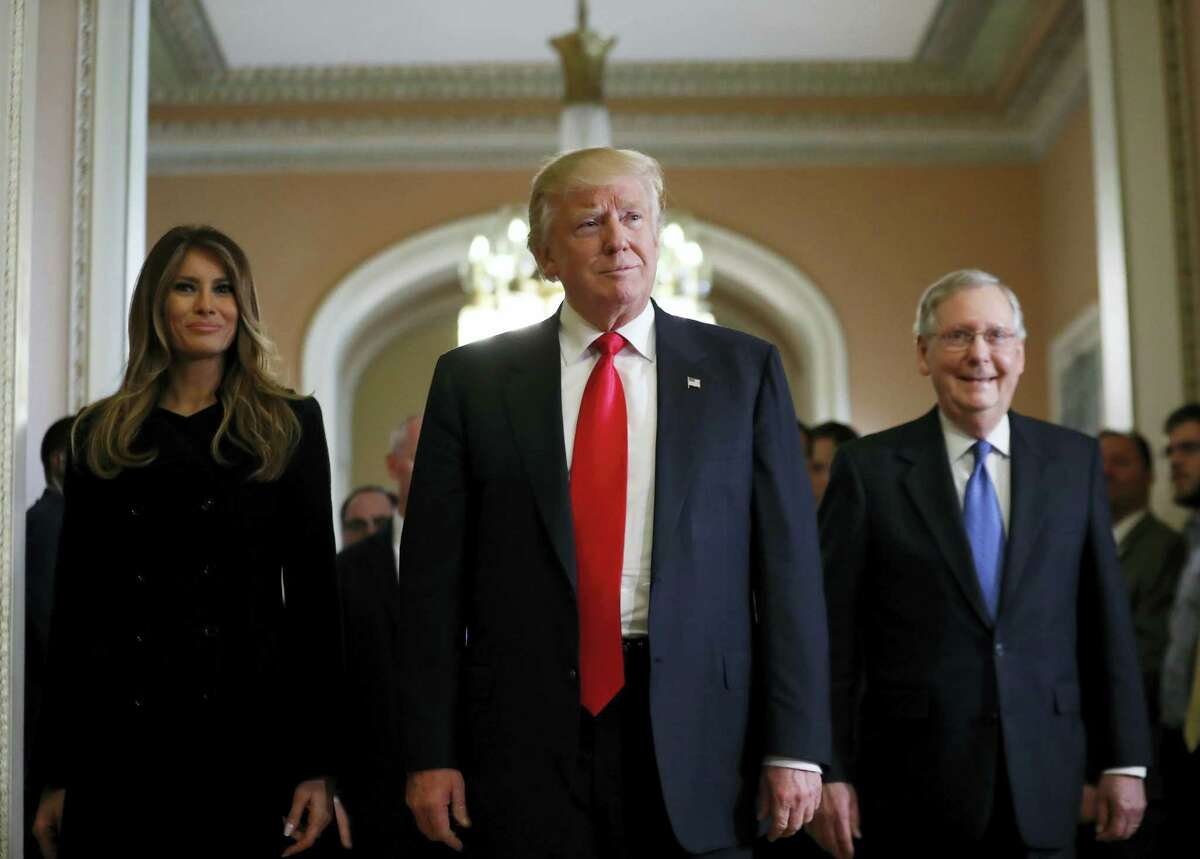 President-elect Donald Trump and his wife Melania walk with Senate Majority Leader Mitch McConnell of Ky. on Capitol Hill Thursday after a meeting.