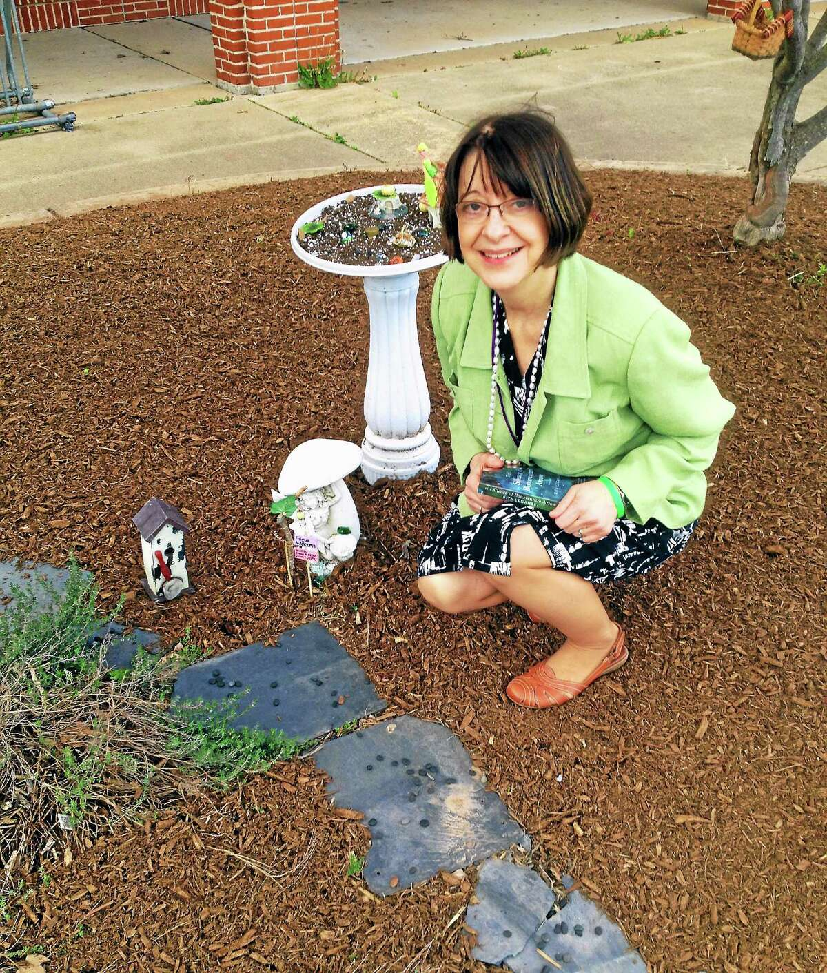 In this 2014 photograph, Cromwell Belden Library Director Eileen Branciforte shows off a whimsical fairy garden created by a patron of the children's department.