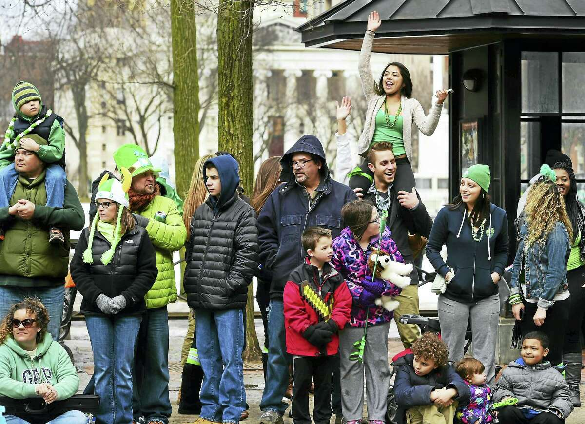 Monica Ghaly of West Haven, on the shoulders of Marcello LaGreca of Branford, waves to marchers in the New Haven St. Patrick's Day Parade in 2015.