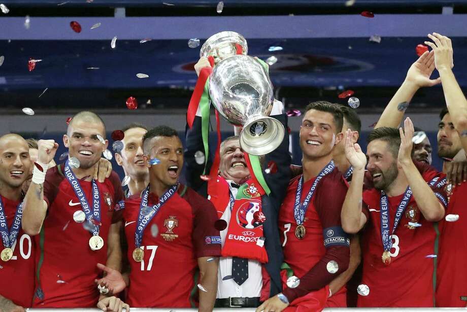 Portugal coach Fernando Santos lifts the trophy between Cristiano Ronaldo, right, and Nani after winning the Euro 2016 final in Saint-Denis, France on Sunday. Photo: Thanassis Stavrakis — The Associated Press  / AP