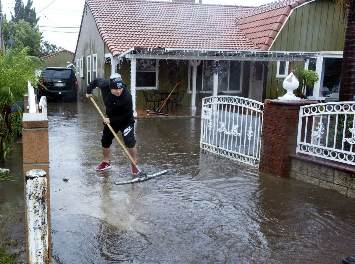 A resident of one of the houses on E. McFadden Avenue in Santa Ana, Calif., squeegees water out of the driveway of the home, Wednesday, Jan. 6, 2016. El Nino storms lined up in the Pacific, promising to drench parts of the West for more than two weeks and increasing fears of mudslides and flash floods in regions stripped bare by wildfires. At least two more storms are expected to follow bringing as much as 3 inches of rain.