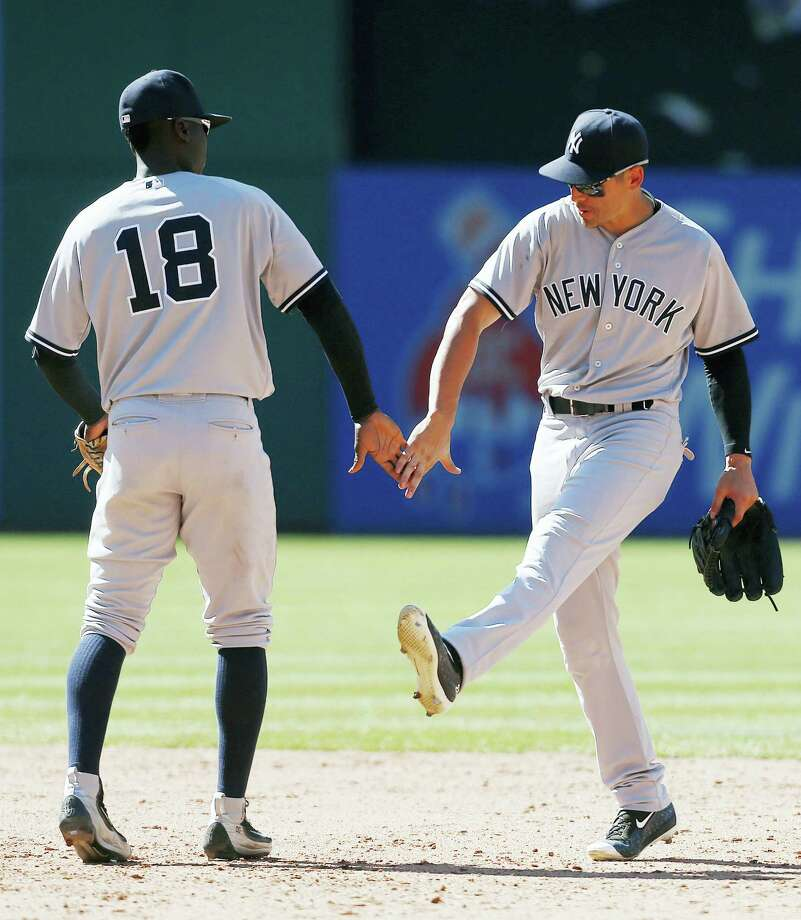 Didi Gregorius (18) and Jacoby Ellsbury celebrate after Sunday's win over the Indians. Photo: Ron Schwane — The Associated Press  / AP 2016