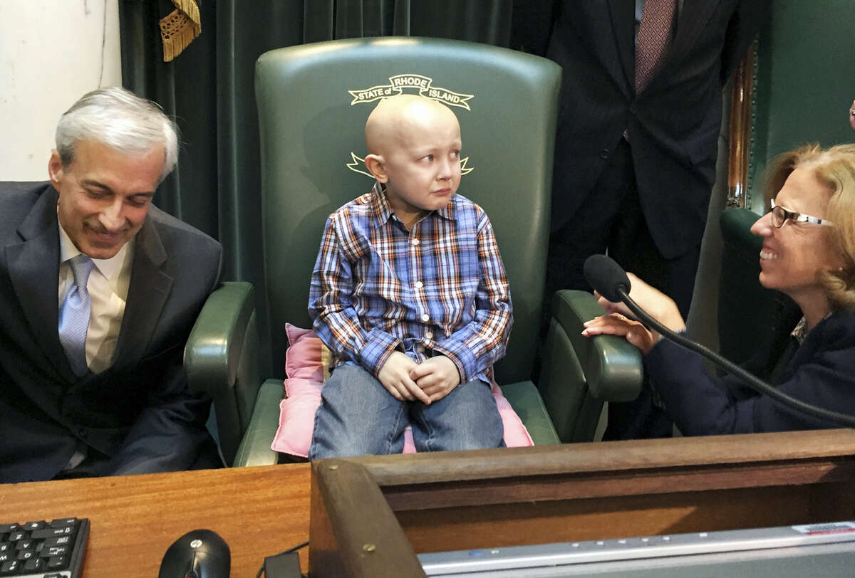 In this Jan. 20, 2016, file photo, Dorian Murray, 8, sits in the Senate Chamber as he is honored by Rhode Island lawmakers including Majority Leader Dennis Algiere, left, and Senate President Teresa Paiva Weed at the Statehouse in Providence, R.I. Murray, of Westerly, R.I., died Tuesday, March 8, 2016, of rare and untreatable form of pediatric cancer. He had told his father that his final wish was to become famous in China.