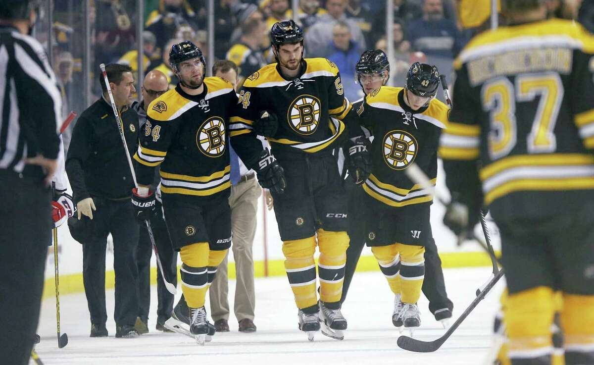 Boston Bruins' Adam McQuaid (54) leaves the ice after being injured during the second period of an NHL hockey game against the Washington Capitals in Boston, Tuesday, Jan. 5, 2016. (AP Photo/Michael Dwyer)
