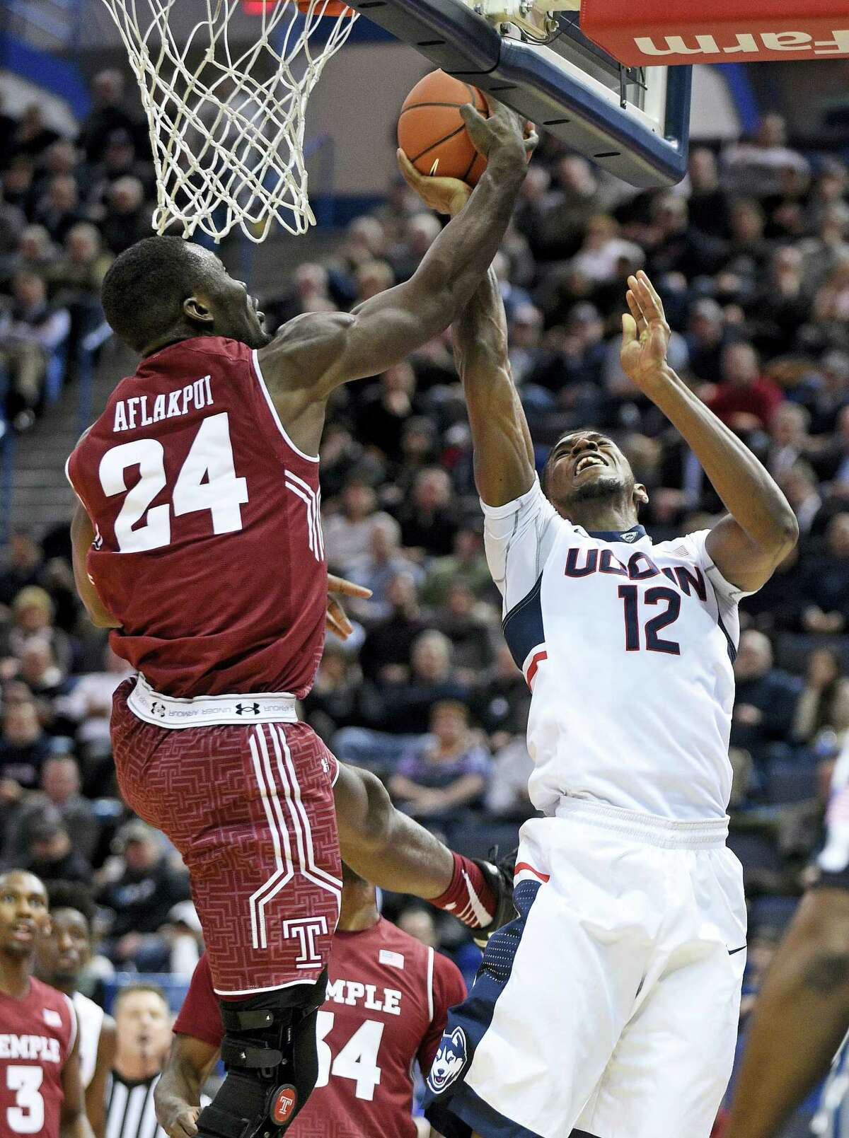 Temple's Ernest Aflakui (24) blocks the shot of Connecticut's Kentan Facey (12) during the first half of an NCAA college basketball game in Hartford, Conn., on Tuesday, Jan. 5, 2016. (AP Photo/Fred Beckham)