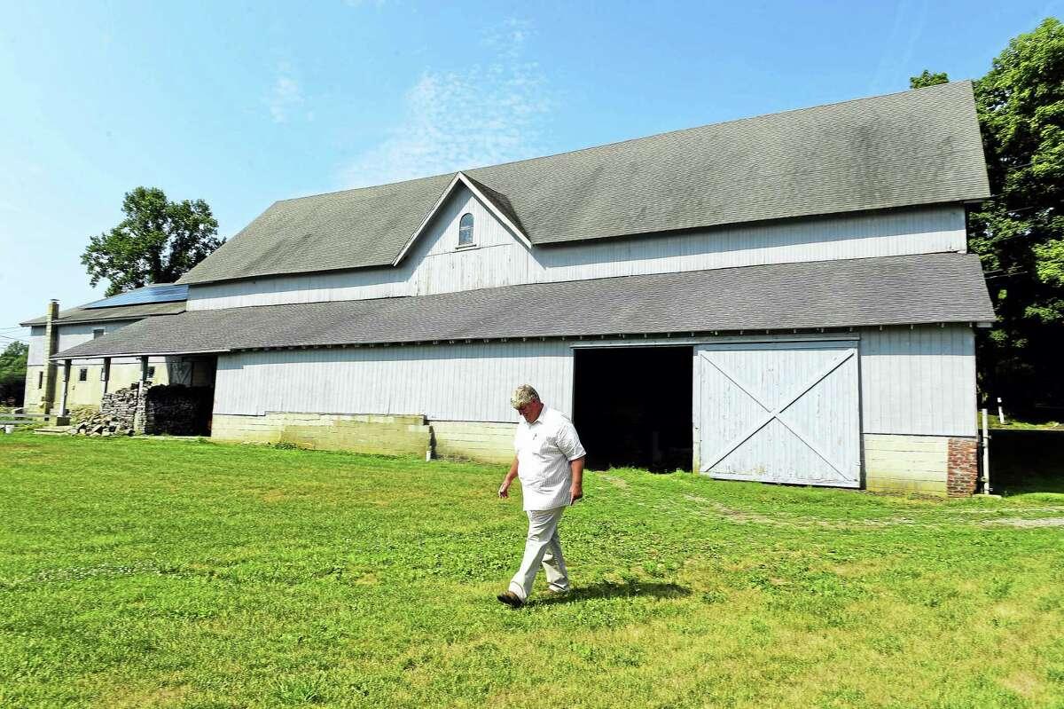 Jim Zeoli of the Shamrock Farm in Orange, and the Orange first selectman, walks by a barn on the farm built in 1896.