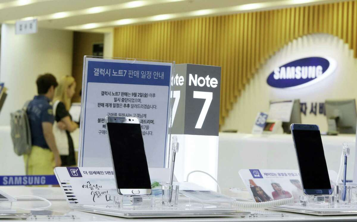 In this Sunday, Sept. 11, 2016 photo, customers wait for recall of their Samsung Electronics Galaxy Note 7 smartphones as powered-off Galaxy Note 7 smartphones are displayed at the company's service center in Seoul, South Korea. Samsung on Tuesday, Sept. 13, 2016, plans to issue a software update for its recalled Galaxy Note 7 smartphones that will prevent them from overheating by limiting battery recharges to under 60 percent.
