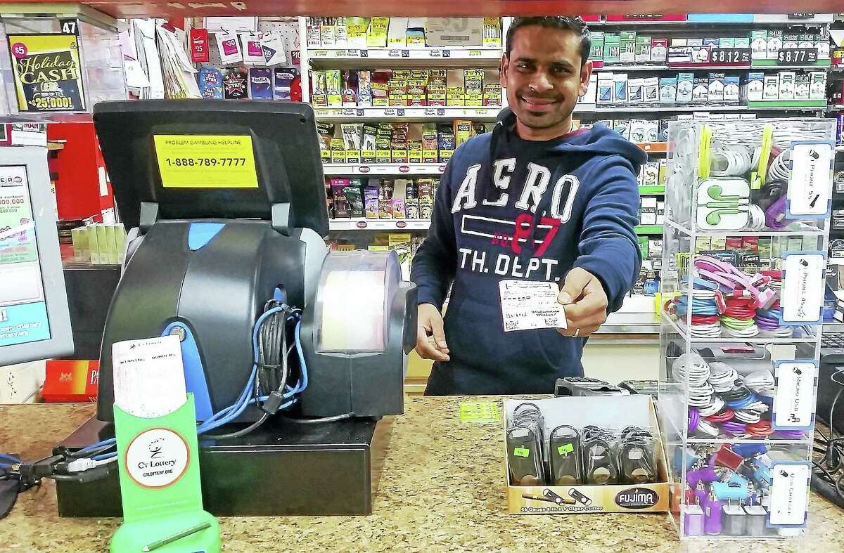 Sanjay Patel holds a Powerball ticket Monday at Krauszers on Route 372, or Berlin Road, in Cromwell. Middlesex County has 128 authorized lottery retailers.
