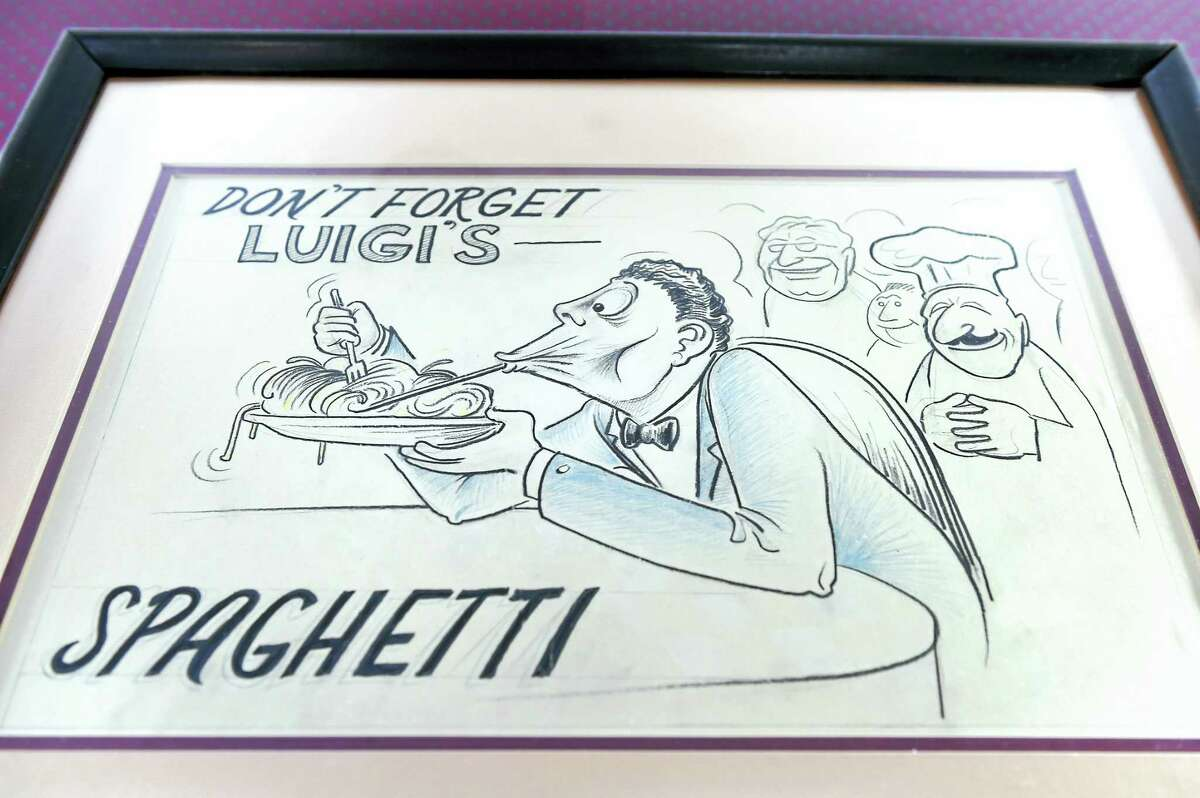Arnold Gold — New Haven Register A cartoon drawing made by a former customer hangs Luigi's.