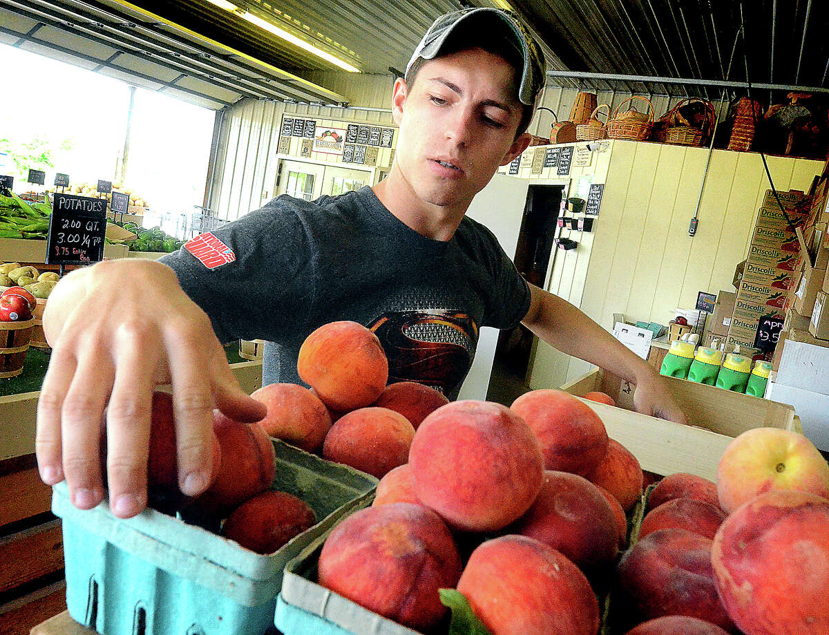 File photo A farmers market employee stocks Garden Beauty peaches for display.