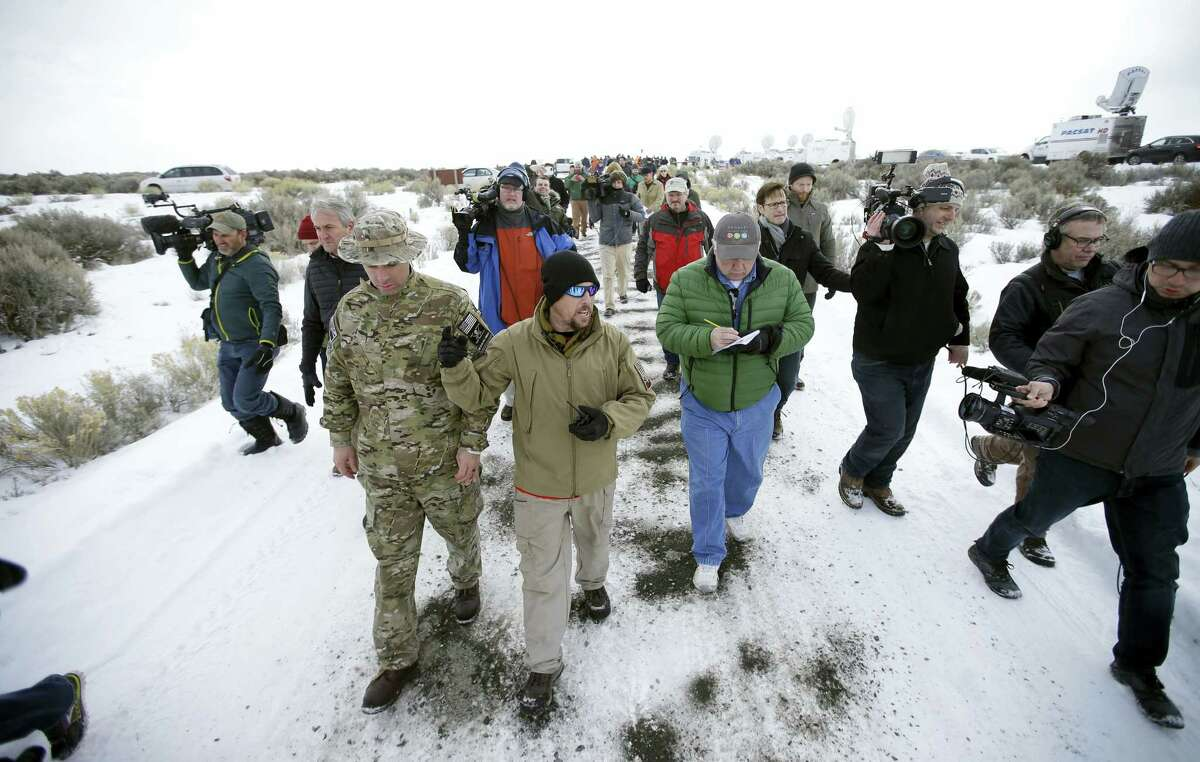 ASSOCIATED PRESS Members of the group occupying the Malheur National Wildlife Refuge headquarters, left, conduct a tour with the media Monday near Burns, Ore.