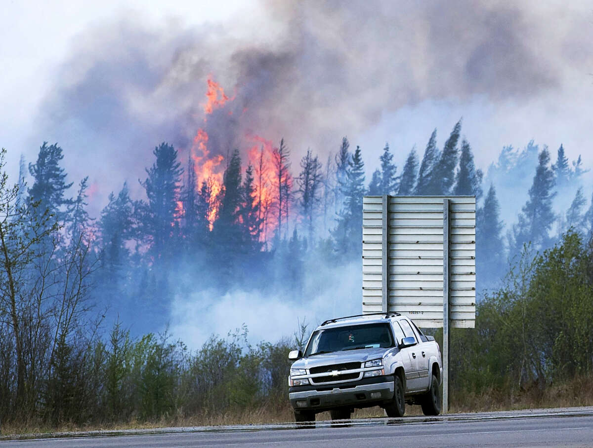 Flames flare up from hotspots along a highway to Fort McMurray, Canada, Sunday, May 8, 2016.