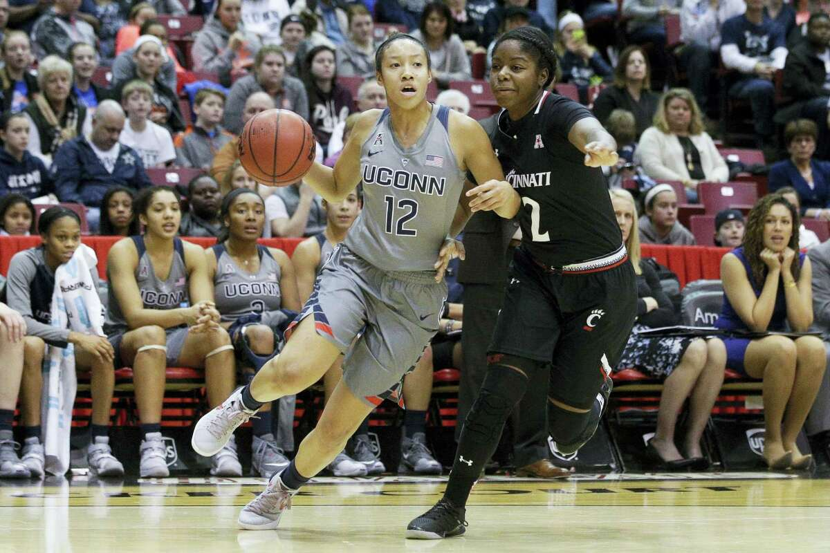 Connecticut's Saniya Chong (12) drives around Cincinnati's Nikira Goings (2) in the second half of an NCAA college basketball game, Wednesday, Dec. 30, 2015, in Cincinnati. Connecticut won 107-45. (AP Photo/John Minchillo)