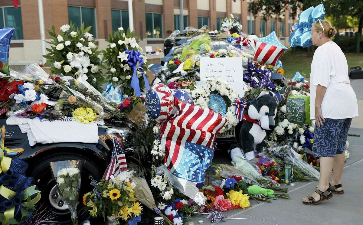 Mary Savage visits a make-shift memorial in front of the Dallas police department Saturday.