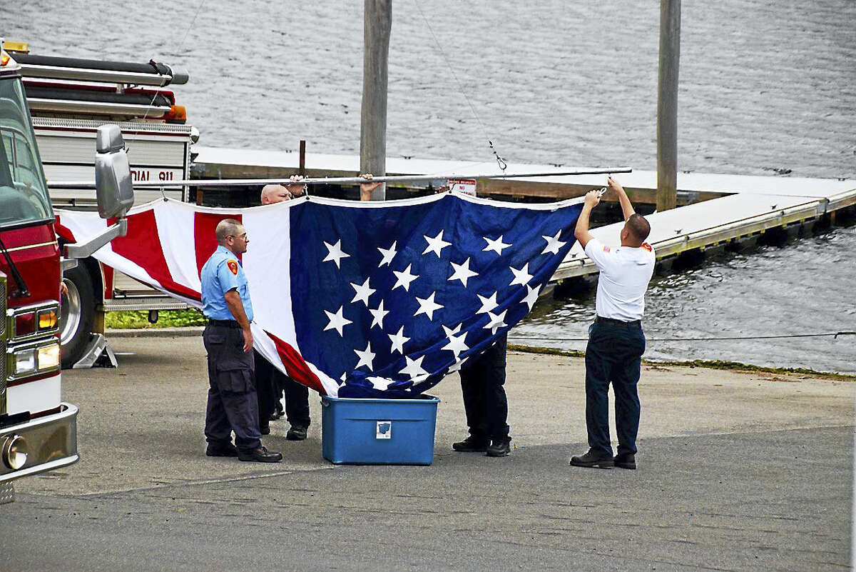 Spectators watch as the massive flag is unfurled Sunday.