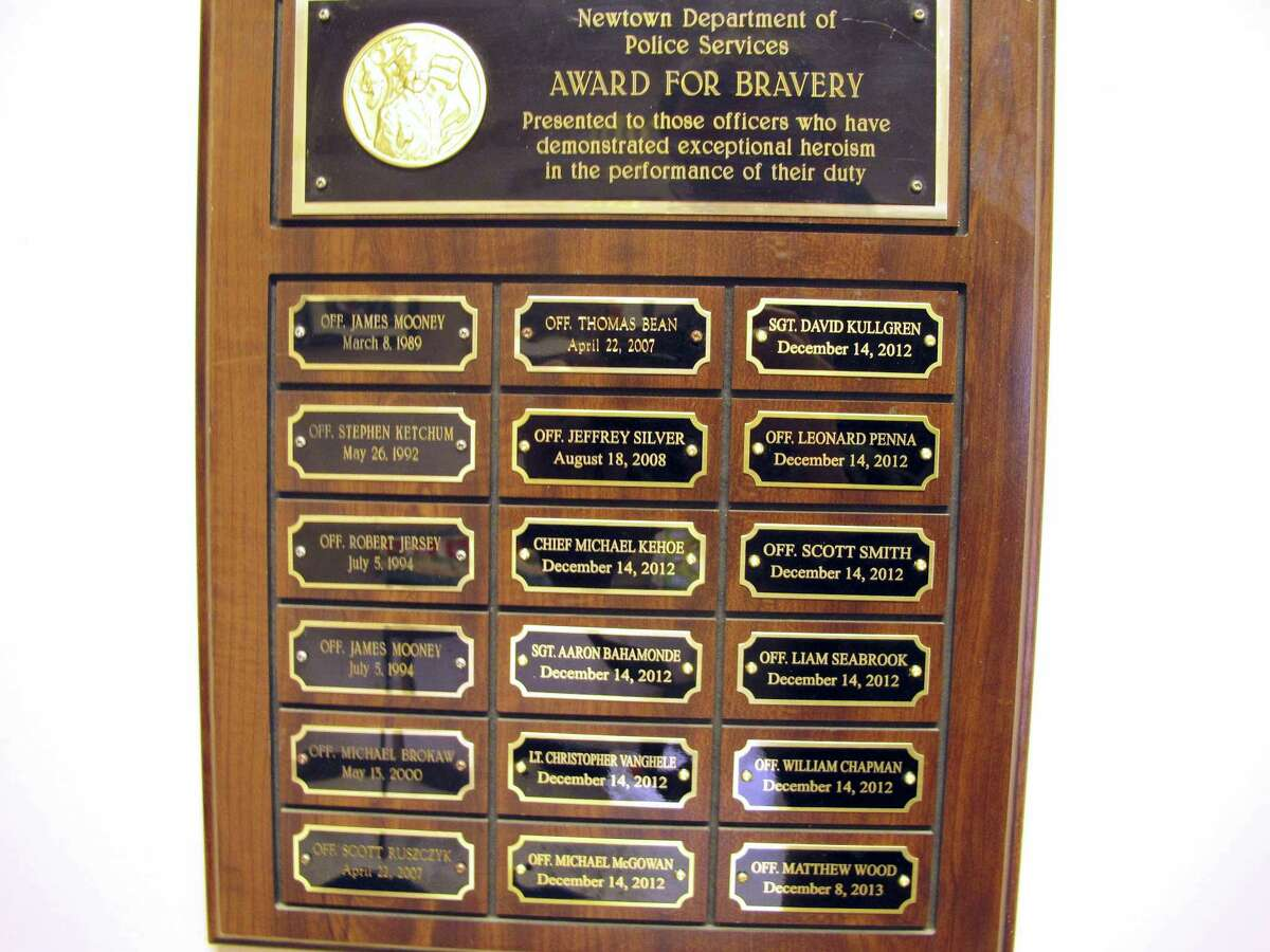 A plaque on the wall of the Newtown, Conn., police department honors officers for their bravery, including Chief Michael Kehoe. Kehoe is retiring Jan. 6, 2016, after 37 years with the town police department.