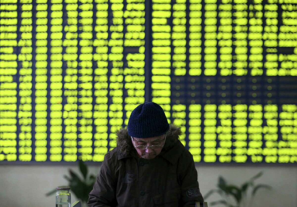 A stock investor pauses near a display board showing stock prices in green to symbolize a fall in price at a brokerage house in Jiujiang in central China's Jiangxi province Monday.