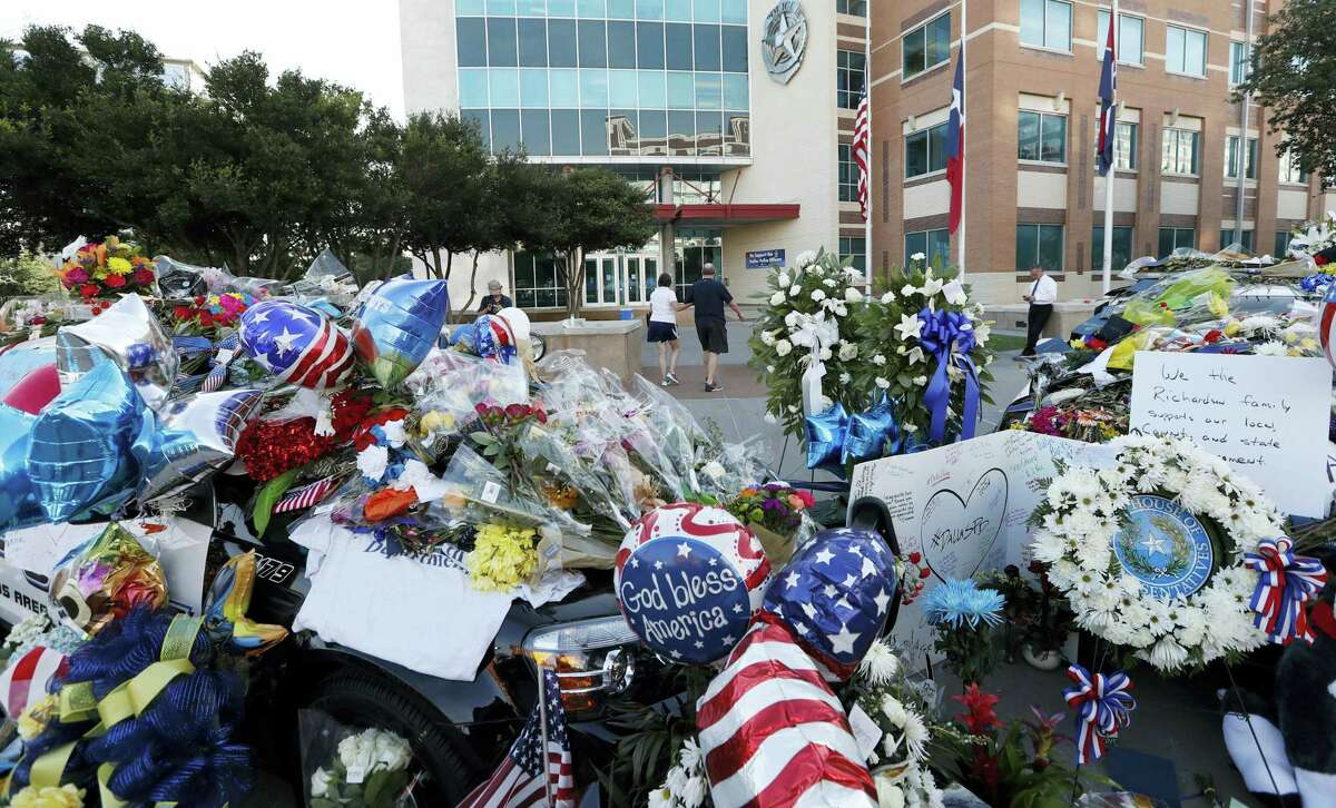 A couple walks away after leaving flowers at a make-shift memorial in front of the Dallas police department, Saturday, July 9, 2016, in Dallas. Five police officers are dead and several injured following a shooting in downtown Dallas Thursday night.