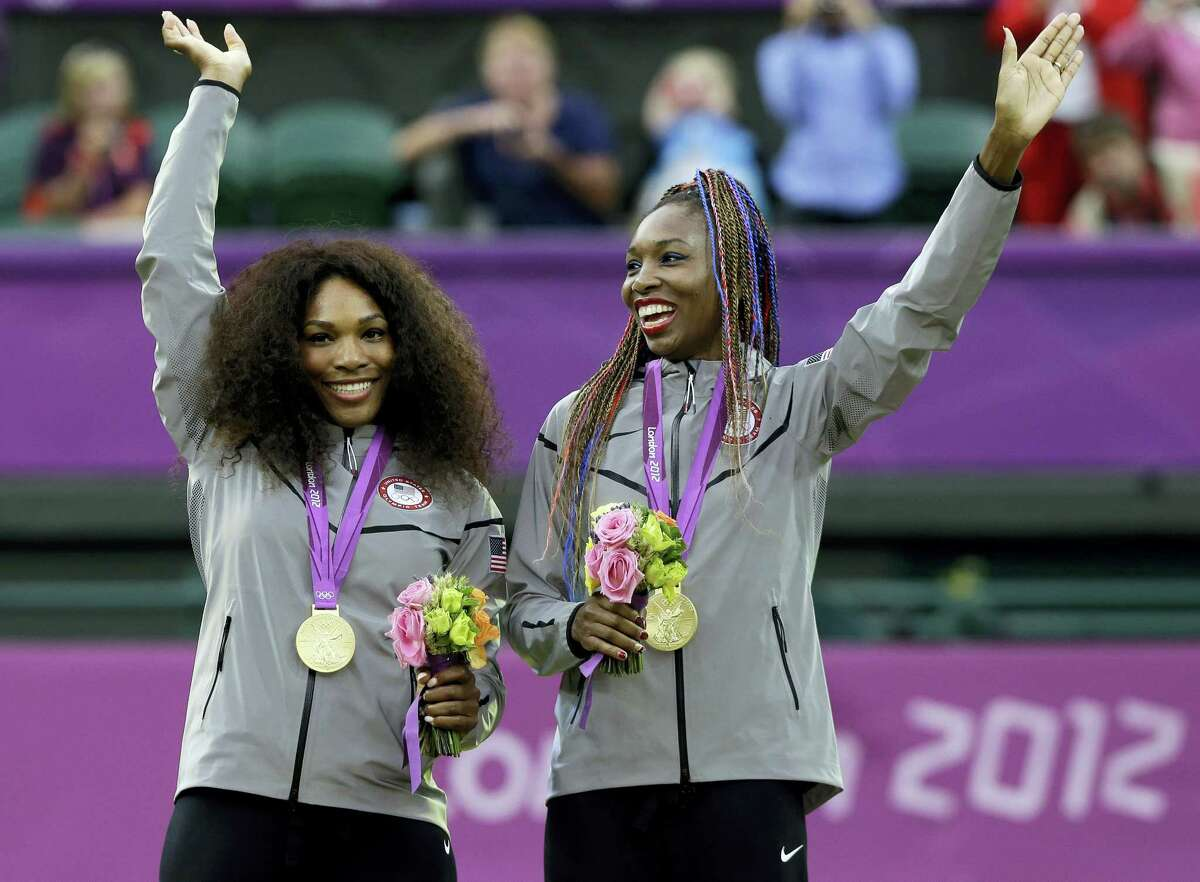 In this photo from the 2012 London Summer Olympics, Serena Williams, left, and Venus Williams of the celebrate on podium after receiving their gold medals in women's doubles. The winningest team in Olympic tennis history has entered the doubles draw at this week's Italian Open to kick off their preparations for the Rio de Janeiro Games.