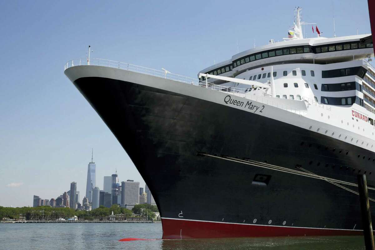 The New York City skyline appears behind the ocean liner Queen Mary 2 as she sits docked at her homeport at the Brooklyn Cruise Terminal in New York.