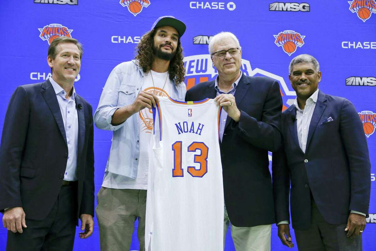 Joakim Noah, center, stands for photos with Knicks coach Jeff Hornacek, left, president Phil Jackson, second from right, and general manager Steve Mills on Friday.