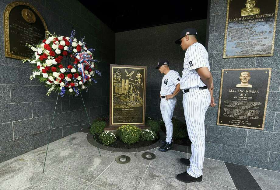 Yankees manager Joe Girardi, left and pitcher Dellin Betances view the September 11th memorial in Monument Park after placing a wreath next to it on Sunday. Photo: Kathy Kmonicek — The Associated Press  / FR170189 AP