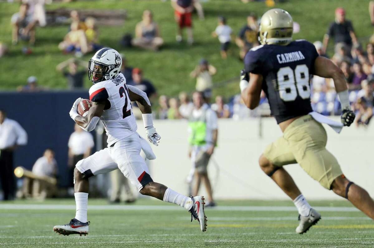 UConn cornerback Jamar Summers, left, looks back he returns a fumble for a touchdown on Saturday.