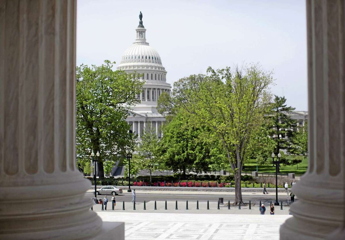 The U.S. Capitol building is seen through the columns on the steps of the Supreme Court in Washington, D.C.
