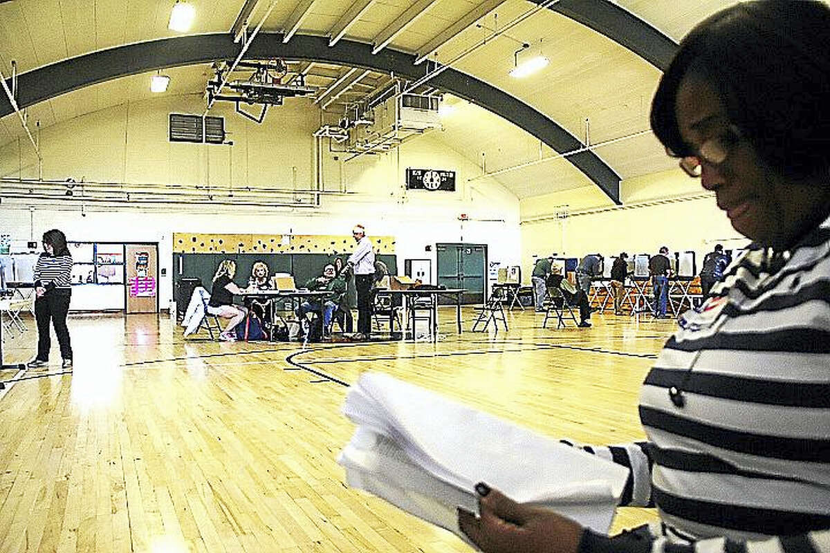 A poll worker directs Middletown voters to sign-in tables at Woodrow Wilson Middle School.