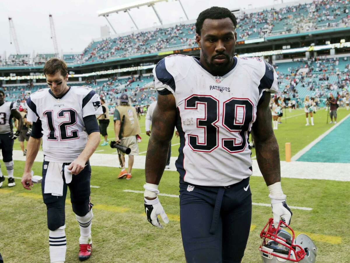 Patriots running back Steven Jackson (39) and quarterback Tom Brady (12) leave the field at the end of Sunday's loss to the Dolphins.
