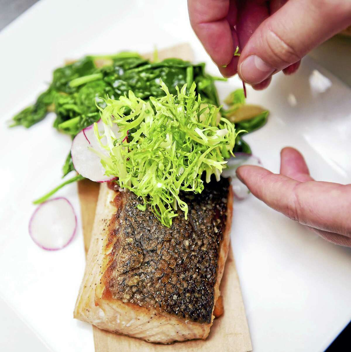 Executive Chef Todd Ruiz of John Davenport's at the Top of the Park prepares cedar plank salmon with garlic spinach topped with a frisee and radish salad.