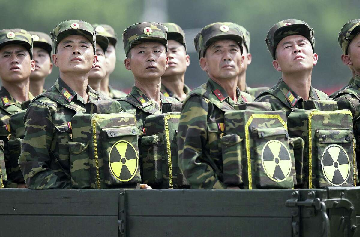 In this July 27, 2013, file photo, North Korean soldiers turn and look towards their leader Kim Jong Un from a military parade vehicle as they carry packs marked with the nuclear symbol during a ceremony marking the 60th anniversary of the Korean War armistice in Pyongyang, North Korea. Mark up another first for North Korea - two nuclear tests in one year.