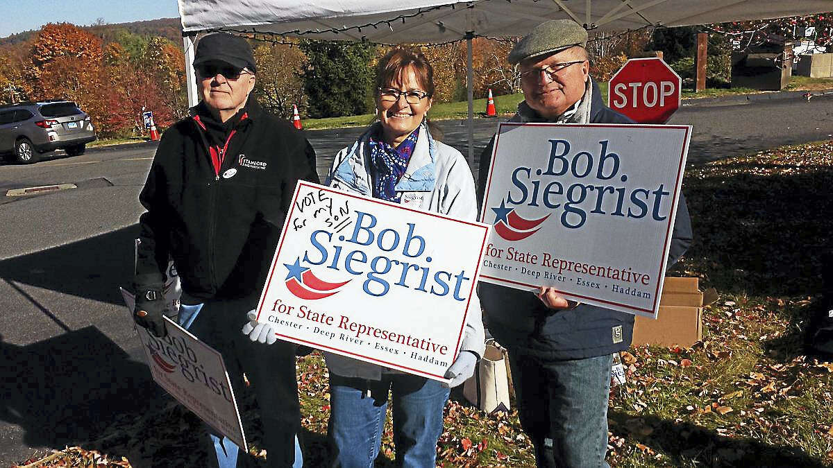 Supporters, including the mother of Senate candidate Republican Bob Siegrist, center, hold up signs Tuesday morning at the Haddam Firehouse.