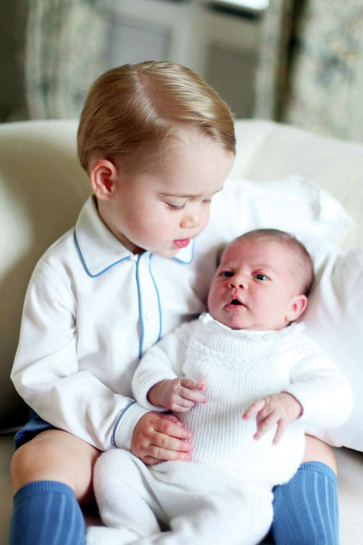 This image made available by Kensington Palace on June 6, 2015, taken by Kate, Duchess of Cambridge, at Amner Hall, eastern England in mid-May 2015 shows Britain's Princess Charlotte, right, being held by her brother, 2-year-old, Prince George.
